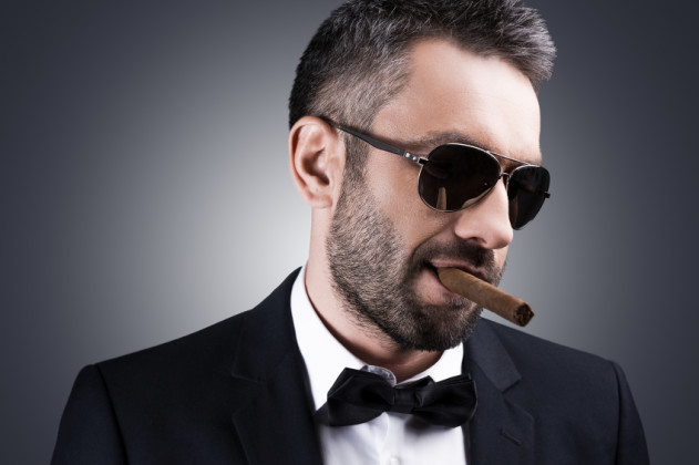 8652f61f0403e Bossy and self-confident. Portrait of handsome mature man in formalwear and  sunglasses smoking cigar and looking away while standing against grey  background